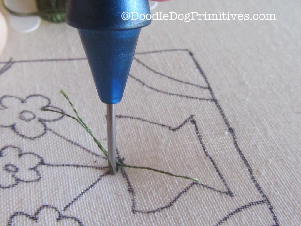 Pushing punch needle into weavers cloth