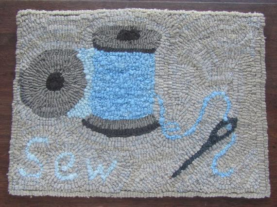 hooked rug with spools of thread and a needle