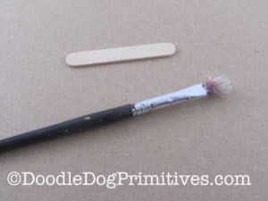 Paint brush and popsicle stick to use in splattering the eggs with paint