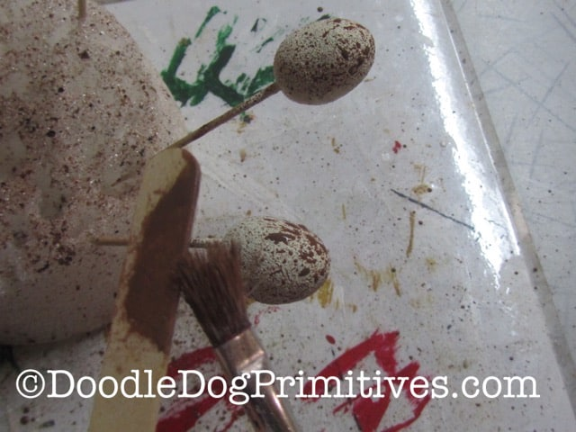 Using the paint brush and popsicle stick to splatter the styrofoam eggs with paint