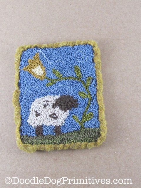 Finished Punch needle project with wool edging